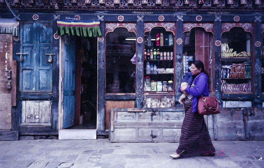 A lady hugging her baby as she walks pass a convenience store in Thimphu City, Bhutan. The colours of Bhutan are vibrant!